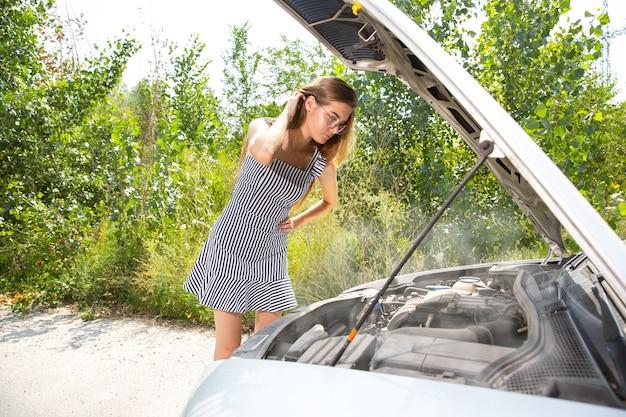 De jonge vrouw gaf de auto pech terwijl ze onderweg was om uit te rusten. ze probeert de kapotte zelf te repareren of zou moeten liften. nerveus worden. weekend, problemen onderweg, vakantie.