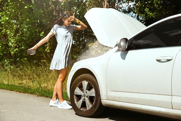 De jonge vrouw gaf de auto pech terwijl ze onderweg was om uit te rusten. ze probeert de kapotte zelf te repareren of zou moeten liften. nerveus worden