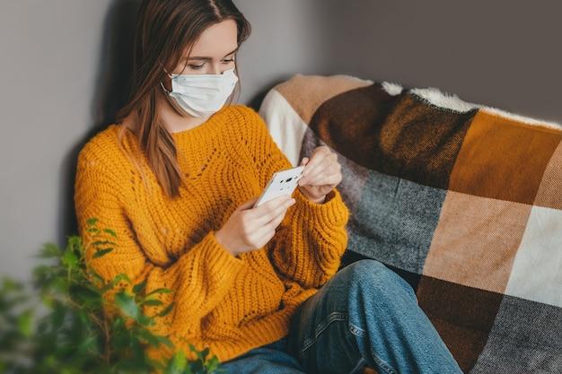 De jonge vrouw gebruikt een mobiele telefoon en zit in een oranje sweater in een medisch in quarantaine thuis geïsoleerd masker en leest het nieuws, exemplaarruimte. meisje werkt thuis en schrijft haar blog