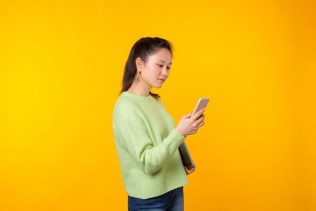 De jonge vrouw gebruikt haar telefoon terwijl het houden van laptop