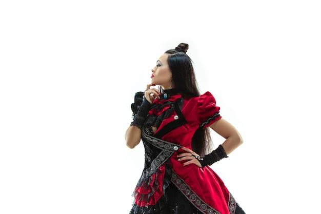 De jonge vrouw gekleed in middeleeuwse stijl die zich voordeed in de studio als markiezin. fantasie, antiek, renaissance-concept