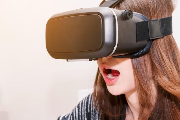 De jonge vrouw geniet thuis van met virtuele werkelijkheidsglazen