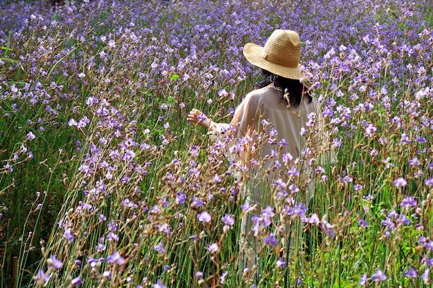 De jonge vrouw geniet van de ochtendgang op mooi purper bloemgebied