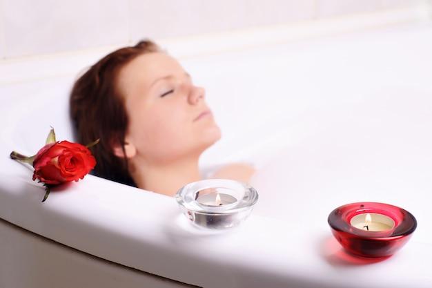 De jonge vrouw geniet van het bad-schuim in de badkuip.