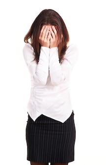 De jonge vrouw heeft gezicht met handen gesloten, dat op wit wordt geïsoleerd