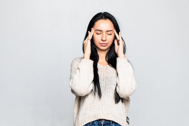De jonge vrouw heeft hoofdpijn die op grijze muur wordt geïsoleerd