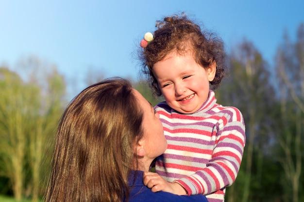 De jonge vrouw heeft pret, glimlacht met haar leuk kindbabymeisje. portret van moeder, klein kind dochter buitenshuis op zonnige zomerdag. moederdag, liefde, geluk, familie, ouderschap, concept kindertijd