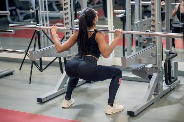 De jonge vrouw heft een barbell op terwijl het uitwerken in een gymnastiek