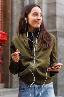 De jonge vrouw het luisteren muziek op oortelefoon maakt aan mobiele telefoon vast