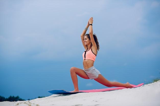 De jonge vrouw het praktizeren yogastrijder stelt dichtbij op het strand van blauwe cloudly hemel