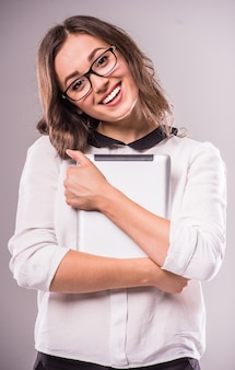 De jonge vrouw houdt digitale tablet en het glimlachen.