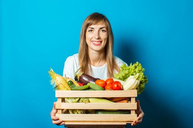 De jonge vrouw houdt een doos met verse groenten op blauw. goed oogstconcept, natuurlijk product