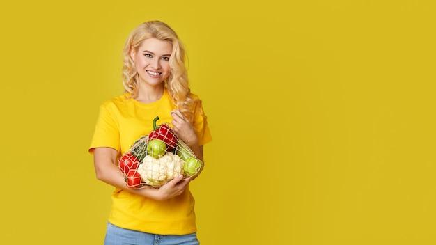 De jonge vrouw houdt een koordzakhoogtepunt van organische groenten op gele muur. blij gezicht. emty ruimte voor tekst. gezond eten, vegetarisme