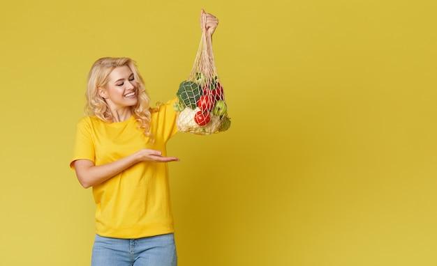 De jonge vrouw houdt een koordzakhoogtepunt van organische groenten op gele muur.