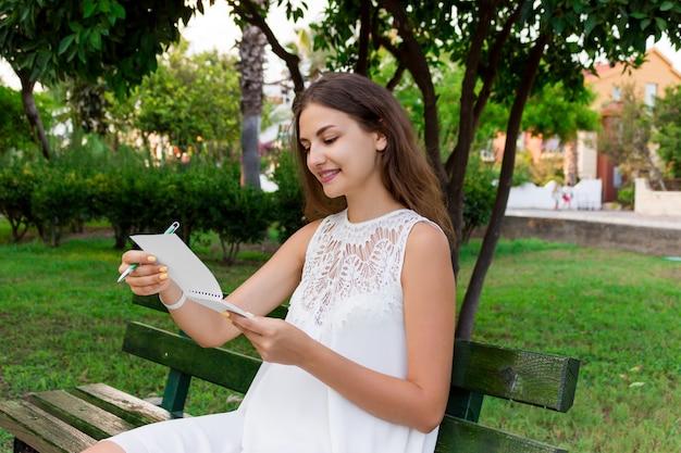 De jonge vrouw houdt een pen en een blocnote en controleert haar programma, ideeën en gedachten die in openlucht stellen