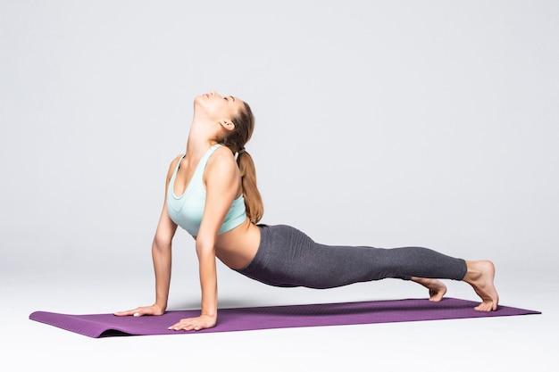 De jonge vrouw houdt een plank op een geïsoleerde mat
