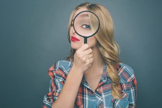 De jonge vrouw houdt een vergrootglas en kijkt er dwars doorheen