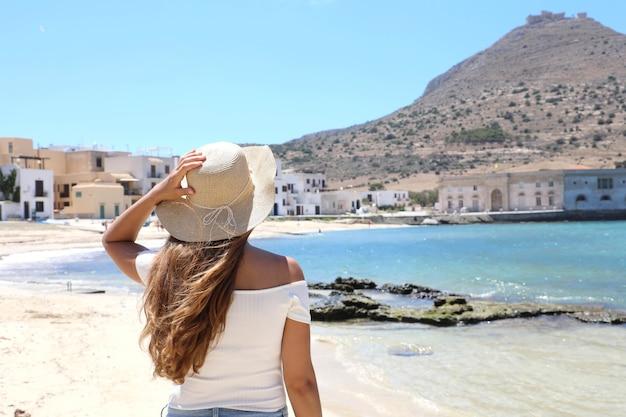 De jonge vrouw houdt hoed en genietend van de berg santa caterina met kasteel bovenop in favignana, sicilië