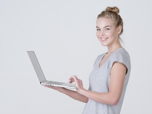 De jonge vrouw houdt laptop in habds. glimlachend kaukasisch meisje met notitieboekje poseren in de studio