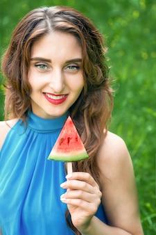 De jonge vrouw houdt stuk van watermeloen zoals ijs op een groene natuur achtergrond.