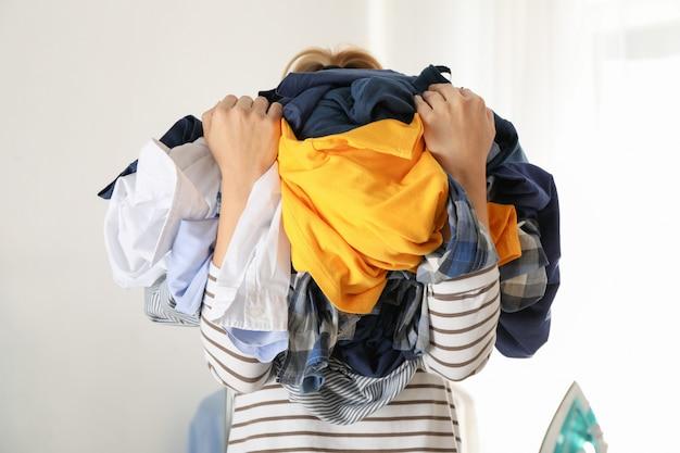 De jonge vrouw houdt verfrommelde kleren,