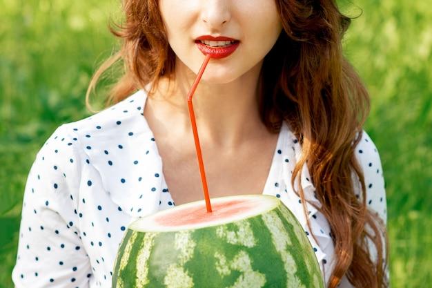 De jonge vrouw houdt watermeloen met cocktailstro dichtbij haar lippen die op gras buiten zitten.