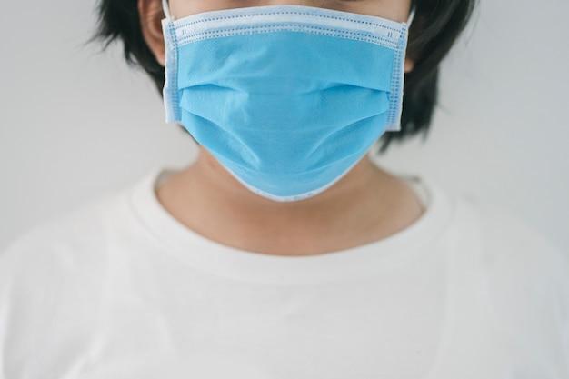 De jonge vrouw in beschermend medisch masker plaatst zich thuis in quarantaine om coronavirus of covid-19 pandemie te stoppen.