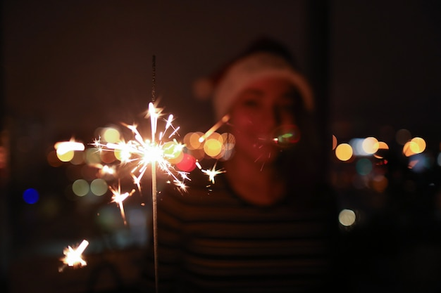 De jonge vrouw in dark houdt aangestoken sterretjes in haar handen.