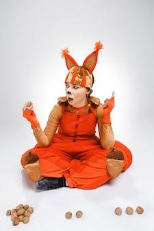 De jonge vrouw in de afbeelding van rode eekhoorn met walnoten. het school- en onderwijsconcept