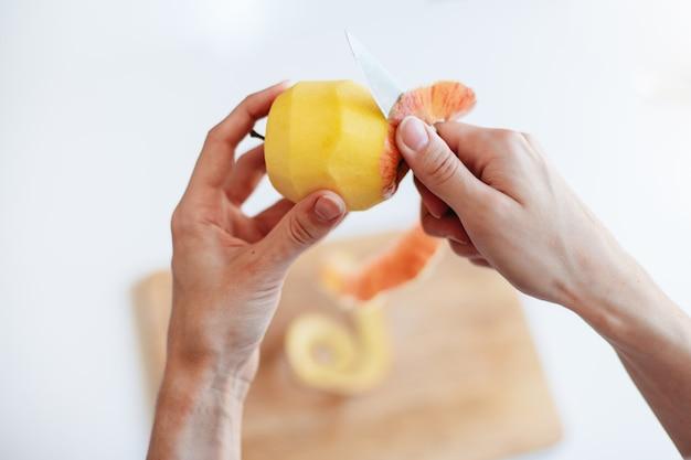 De jonge vrouw in de keuken pelt en snijdt een appel