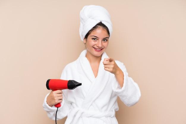 De jonge vrouw in een badjas met haardroger over geïsoleerde muur richt vinger op u met een zekere uitdrukking