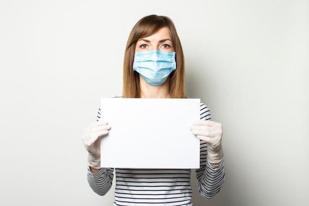 De jonge vrouw in een beschermend medisch masker en latexhandschoenen houdt een wit blad voor zich op een licht geïsoleerde muur. emotioneel gezicht. quarantaine, remedies, coronavirusconcept. kopieer ruimte