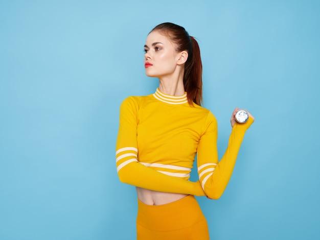 De jonge vrouw in een helder geel sportkostuum met domoren doet sporten op een blauwe ruimte