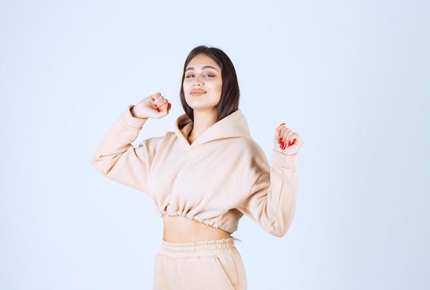 De jonge vrouw in een roze hoodie ziet er moe en slaperig uit