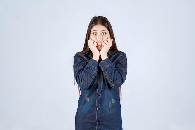 De jonge vrouw in een spijkeroverhemd ziet er bang en bang uit