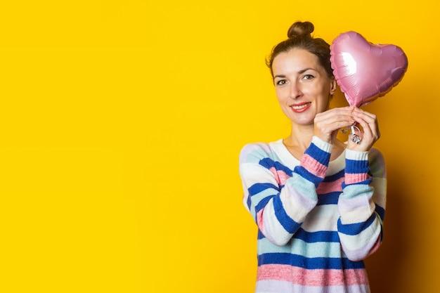 De jonge vrouw in een sweater houdt een hart van de luchtballon op een gele achtergrond. valentijnsdag samenstelling.