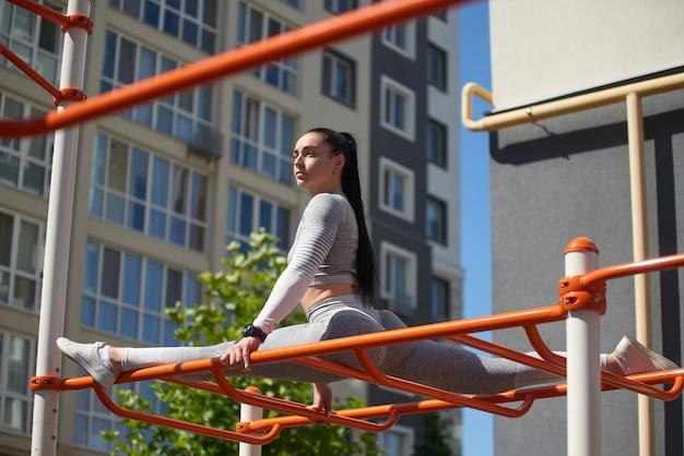 De jonge vrouw in een trainingspak zit aan een touw bovenop een metalen structuur en kijkt opzij.
