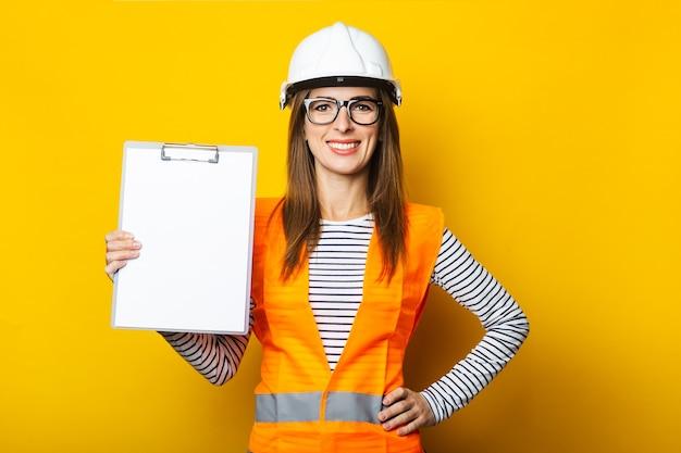 De jonge vrouw in een vest en bouwvakker houdt een klembord op geel