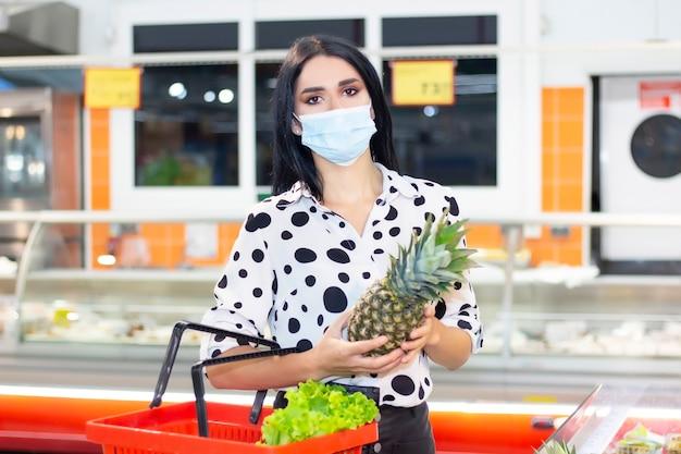 De jonge vrouw in een wegwerp medisch masker winkelt bij de supermarkt. fruit kopen