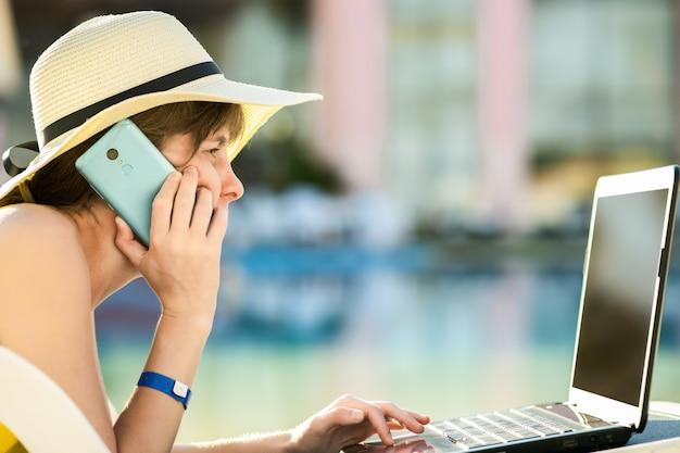 De jonge vrouw in gele kleding legt op strandstoel die aan computerlaptop werkt die gesprek op mobiele telefoon in de zomertoevlucht heeft.