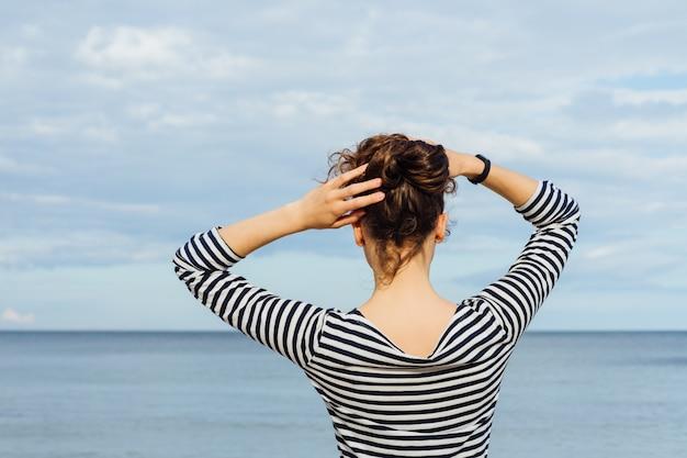 De jonge vrouw in gestreepte t-shirt en met krullend haar die het overzees bekijken en houdt haar haar