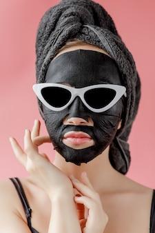 De jonge vrouw in glazen past zwart kosmetisch stoffen gezichtsmasker op roze muur toe. gezichtspeeling masker met houtskool, spa schoonheidsbehandeling, huidverzorging, cosmetologie. detailopname