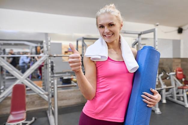 De jonge vrouw in gymnastiek het tonen beduimelt omhoog