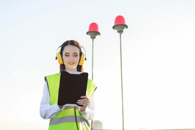 De jonge vrouw in het groene westen en de oorbeschermers bevinden zich op dak, greeptablet