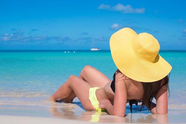 De jonge vrouw in hoed op het strand geniet van caraïbische vakantie