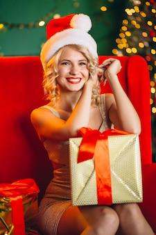 De jonge vrouw in kleding met kerstmis stelt zittend op bank voor