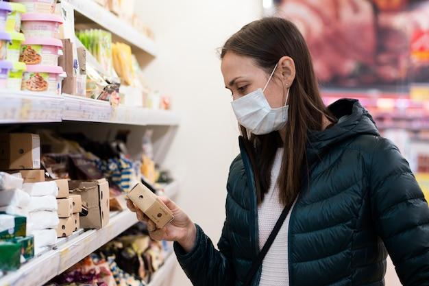 De jonge vrouw in medisch masker koopt een zuivelfabriek bij supermarkt