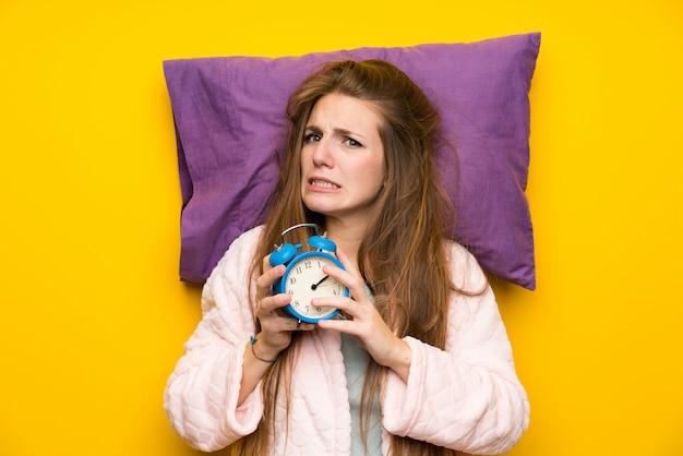 De jonge vrouw in peignoir in een bed beklemtoonde het houden van uitstekende klok