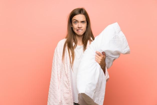 De jonge vrouw in peignoir over roze muur die twijfels hebben en met verwart gezichtsuitdrukking