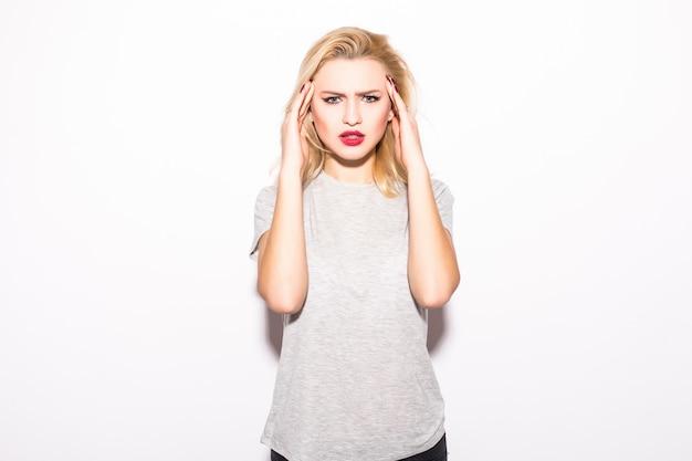 De jonge vrouw in pijn heeft tandpijn die op witte muur wordt geïsoleerd